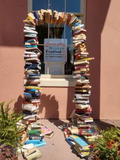 "Archway made of books framing a sign that reads ""Emerging Writers Festival 2019, Old Town Alexandria, VA"""