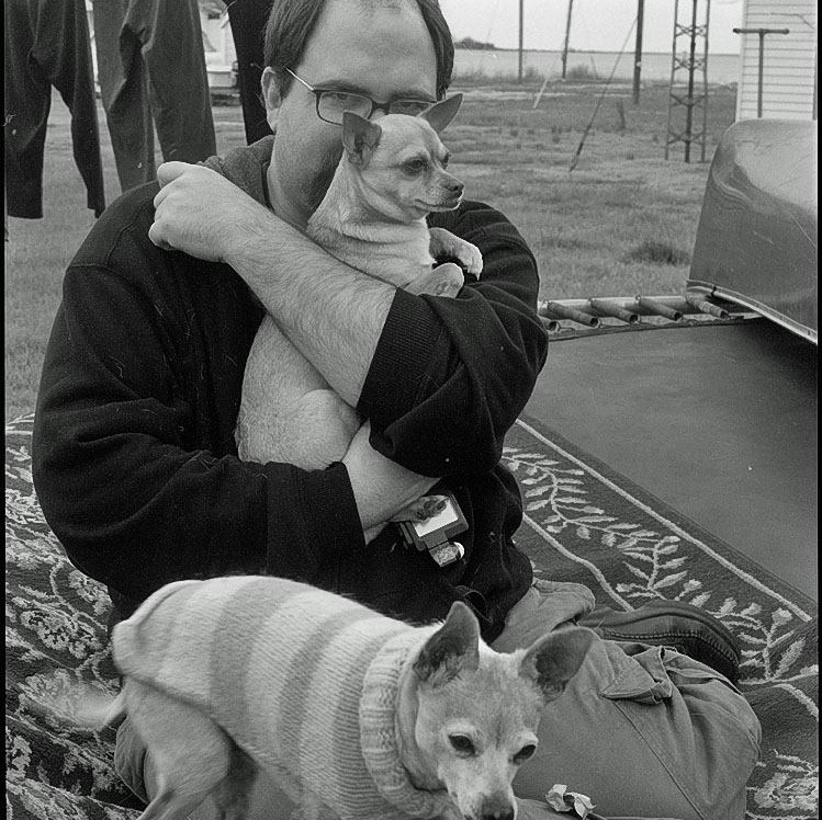 Black and white photograph of man seated on ground with two small dogs