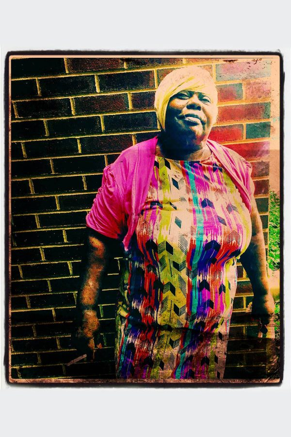 Color photograph of woman wearing bright colors, standing in front of a brick wall