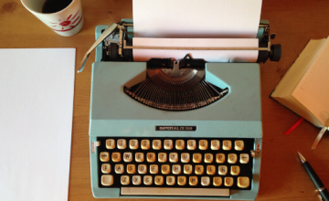 Cover image of a coffee cup, a teal typewriter, and a journal with a pen all lying on a table