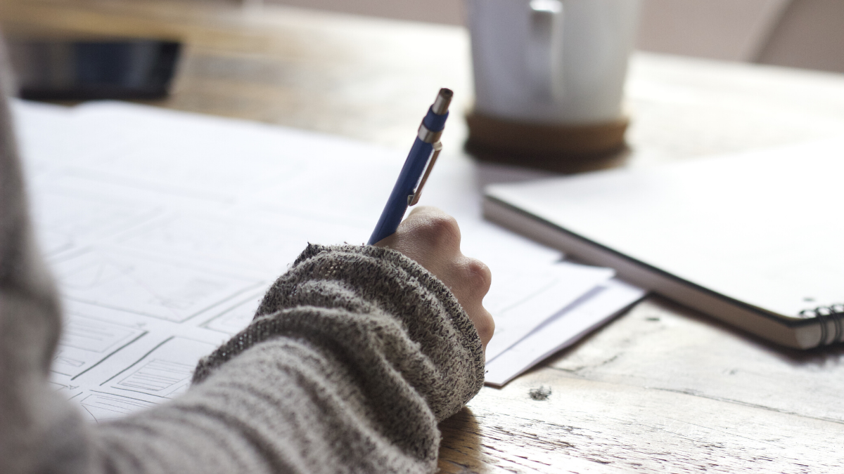 Close-up photograph of a woman's hand writing on some papers. A notebook and coffee mug litter the table beside her.