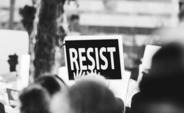 "Black and white photograph of a protest. The only thing in focus is a woman's hands holding a sign that says ""Resist."""